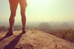 Woman hiker legs on  mountain peak rock Stock Images