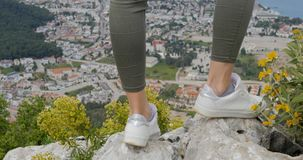 Woman hiker legs stand on mountain peak rock. Kemer city on the background, Turkey stock video