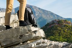 Woman hiker legs stands on the edge of the mountain cliff against beautiful mountains peak stock photos