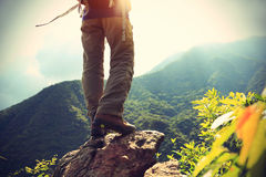 Woman hiker legs on sunrise mountain Royalty Free Stock Images