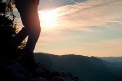 Woman hiker legs in tourist boots stand on mountain rocky peak. Sun n background Stock Photos