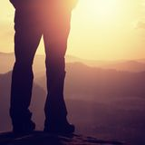 Woman hiker legs in tourist boots stand on mountain rocky peak. Sunny day Royalty Free Stock Images