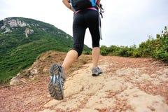 Woman hiker legs walking on seaside mountain trail Stock Images