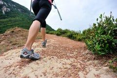 Woman hiker legs walking on seaside mountain trail Stock Photos