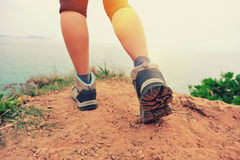 Woman hiker legs walking on seaside mountain trail Royalty Free Stock Photos