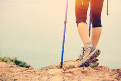 Woman hiker legs walking on seaside mountain trail Stock Photos