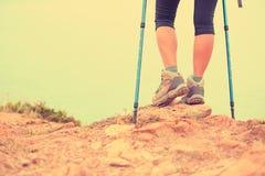 Woman hiker legs walking on seaside mountain trail Royalty Free Stock Photo