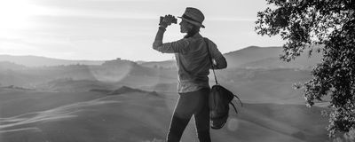 Woman hiker looking into the distance through binoculars. Discovering magical views of Tuscany. Full length portrait of adventure woman hiker with bag enjoying Stock Photos