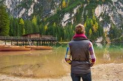 Woman hiker looking out at wooden boats and pier on Lake Bries. A brunette woman hiker, wearing outdoor gear is standing looking out at the view on Lake Bries Stock Photography