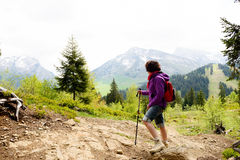 Woman hiker looks at the top of the mountain Stock Photography