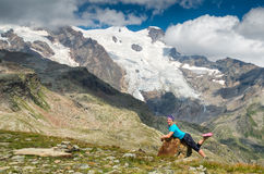 Woman hiker lying on the rock beside Alp glacier, Italy. Happy girl at Alpine landscape, Italy, Monte rosa Stock Photos