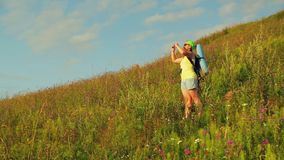 Woman hiker on the mountain with a backpack behind him and binoculars photographs nature on the phone. Overall plan stock video