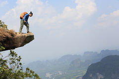 Woman hiker on mountain peak cliff. Young woman hiker on mountain peak cliff stock photography