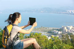 Woman hiker use digital tablet mountain peak Royalty Free Stock Photo