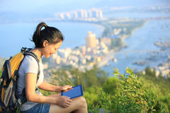 Woman hiker mountain peak use tablet pc Stock Image