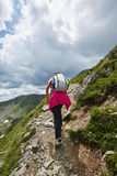 Woman hiker on a mountain trail Stock Images
