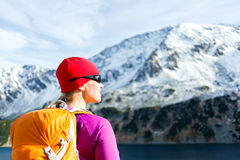 Woman hiker in mountains. Hiking woman in mountains. Fitness and healthy lifestyle outdoors in winter nature. Young female with sunglasses smiling and looking at Royalty Free Stock Images
