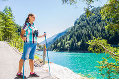 Woman hiker in the mountains looks at the telescope Royalty Free Stock Image