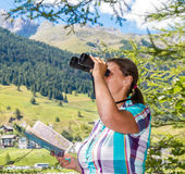 Woman hiker in the mountains looks at the telescope Stock Photography