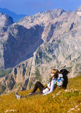Woman Hiker in Mountains relaxing on grass with backpack Royalty Free Stock Images