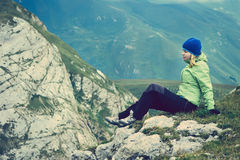 Woman Hiker in Mountains relaxing on rocky cliff outdoor Royalty Free Stock Images