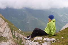 Woman Hiker in Mountains relaxing sitting on rocky cliff Stock Photography