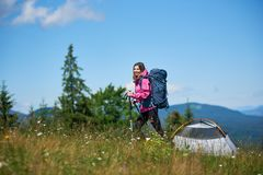 Woman hiker near camping in the mountains with backpack and trekking sticks in the morning. Young smiling woman hiker with blue backpack and trekking sticks near Royalty Free Stock Photography