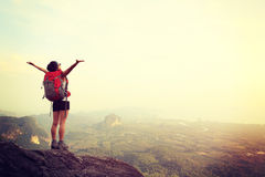 Woman hiker open arms. Cheering woman hiker open arms at mountain peak Stock Photo