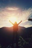 Woman hiker open arms at mountain peak Stock Photos