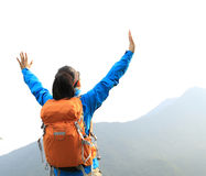 Woman hiker open arms at mountain peak cliff Stock Photo
