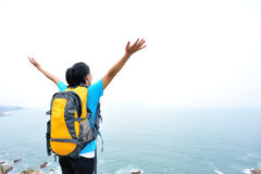 Woman hiker open arms seaside Stock Image