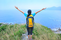 Woman hiker open arms seaside Royalty Free Stock Images
