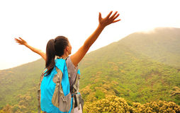 Woman hiker open arms at sunrise mountain peak Stock Photos