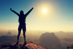 Woman hiker open arms on sunrise mountain top royalty free stock image