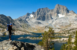 Woman Hiker Overlooking Alpine Lake and Skyline. Stock Images