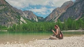 Woman hiker with photocamera sits on the shore of Lago di Braies, Dolomites, Italy stock video footage