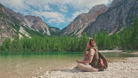 Woman hiker with photocamera sits on the shore of Lago di Braies, Dolomites, Italy stock footage
