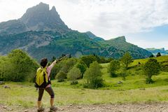 Woman hiker with Pic du Midi d`Ossau in the French Pyrenees. A woman hiker with Pic du Midi d`Ossau in the French Pyrenees Royalty Free Stock Image