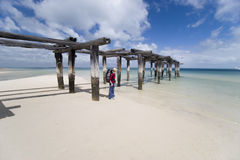 Woman hiker by pier 1. Female hiker standing on beach in australia by pier on fraser island Royalty Free Stock Image