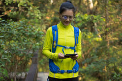 Woman hiker reading ebook on forest trail while have rest Stock Photos