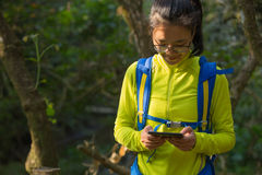 Woman hiker reading ebook on forest trail while have rest Stock Photography