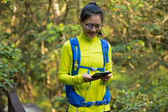 Woman hiker reading ebook on forest trail while have rest Royalty Free Stock Images