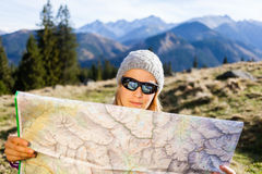 Woman hiker reading map in mountains Royalty Free Stock Image
