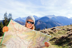 Woman hiker reading map in mountains royalty free stock photography