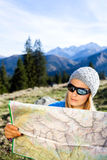 Woman hiker reading map in mountains Stock Images