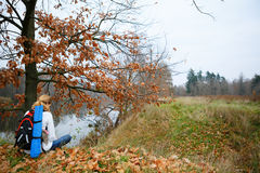 Woman hiker relax on the autumn riverside Stock Images