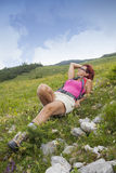 Woman hiker resting, lying high in the mountain Stock Image