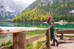 Woman hiker rests on a wooden railing, facing Lake Bries Stock Image