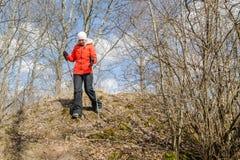 Woman hiker with scandinavian sticks walks at sunset stock image
