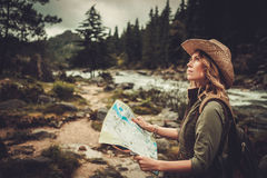 Woman hiker, searching right direction on map near wild mountain river Royalty Free Stock Image